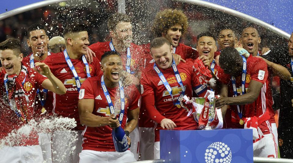 Manchester United F.C. players celebrate after receiving the league Cup trophy.