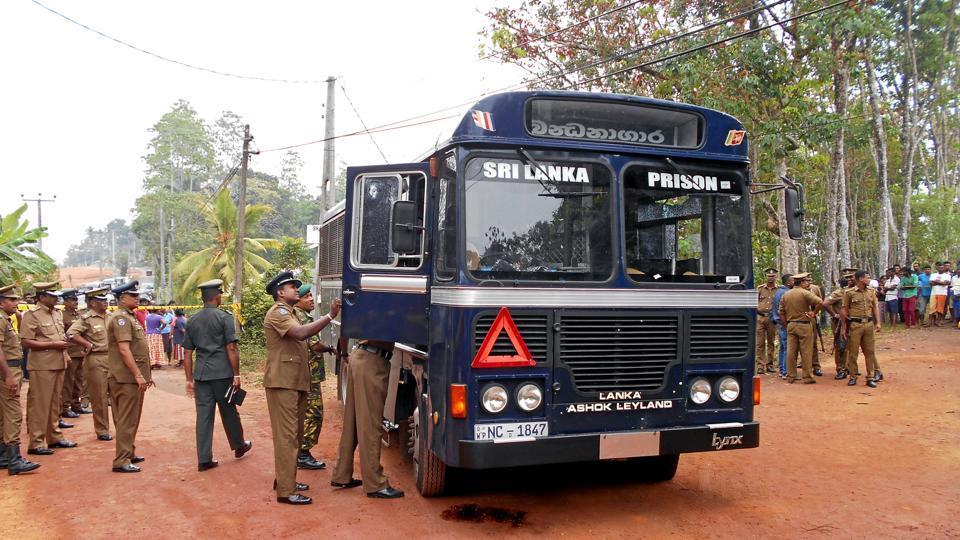 Sri Lanka's police officers inspect a prison bus after gunmen opened fire in Colombo, Sri Lanka.