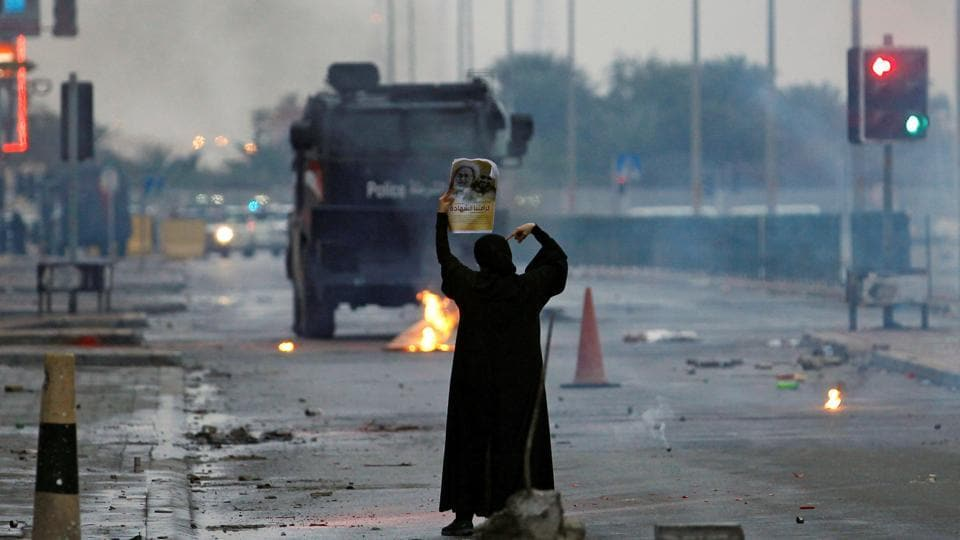 A female protester holds a photo of Shia scholar Isa Qassim as she confronts riot police armoured personnel carrier during a demonstration to mark the 6th anniversary of the February 14 uprising, in the village of Sitra, Bahrain.