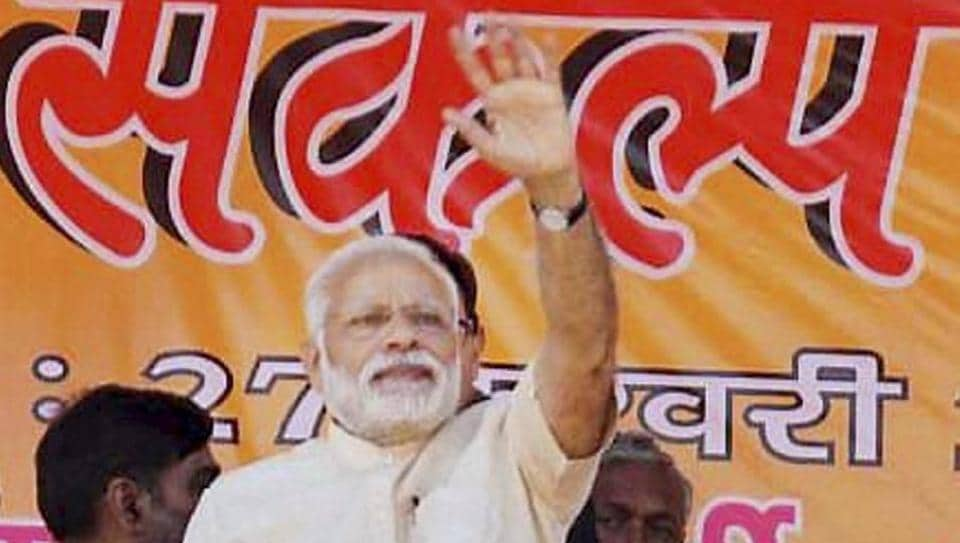 Prime Minister Narendra Modi waves to the crowd at an election rally at Mau in Uttar Pradesh on Monday.