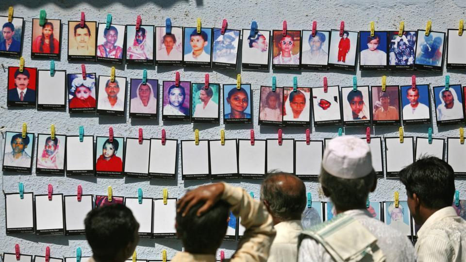 Survivors look at the pictures of the Godhra riots victims at a photo-exhibition held to commemorate its 10th anniversary in Ahmedabad, February 27, 2012.