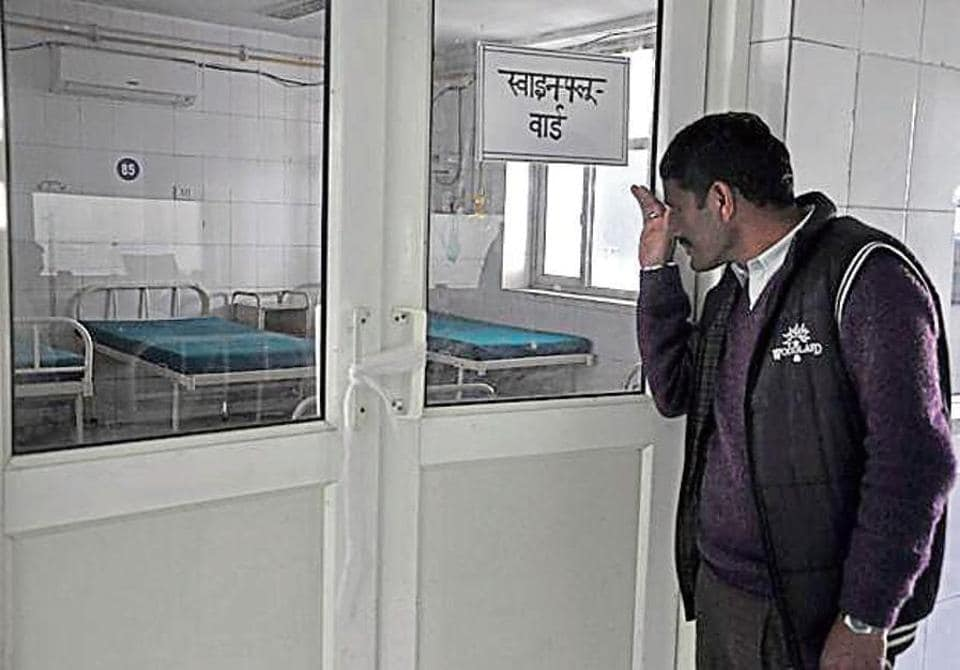 A man looks inside an isolation ward for H1N1 atients at the Doon Medical College Hospital in DehradunCaption