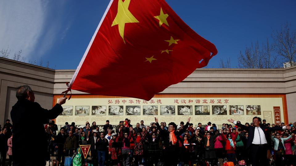 A man waves the Chinese national flag as an amateur choir performs in a park in a residential neighbourhood in Beijing on February 28, 2017.