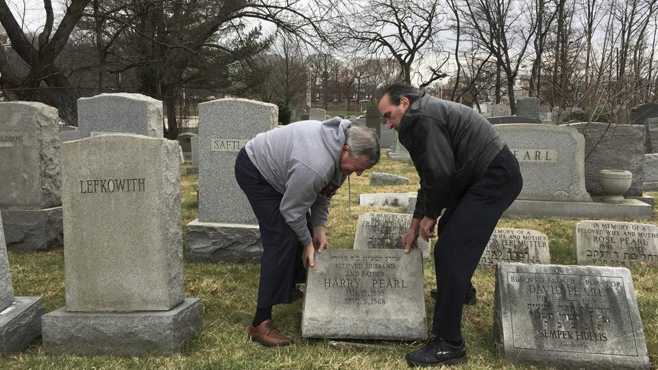 Philadelphia Mayor Jim Kenney, left, helps David Pearl Jr. lift up the headstone of Pearl's grandfather, as he surveys the damage at Mount Carmel Cemetery Monday, Feb. 27, 2017, in Philadelphia.