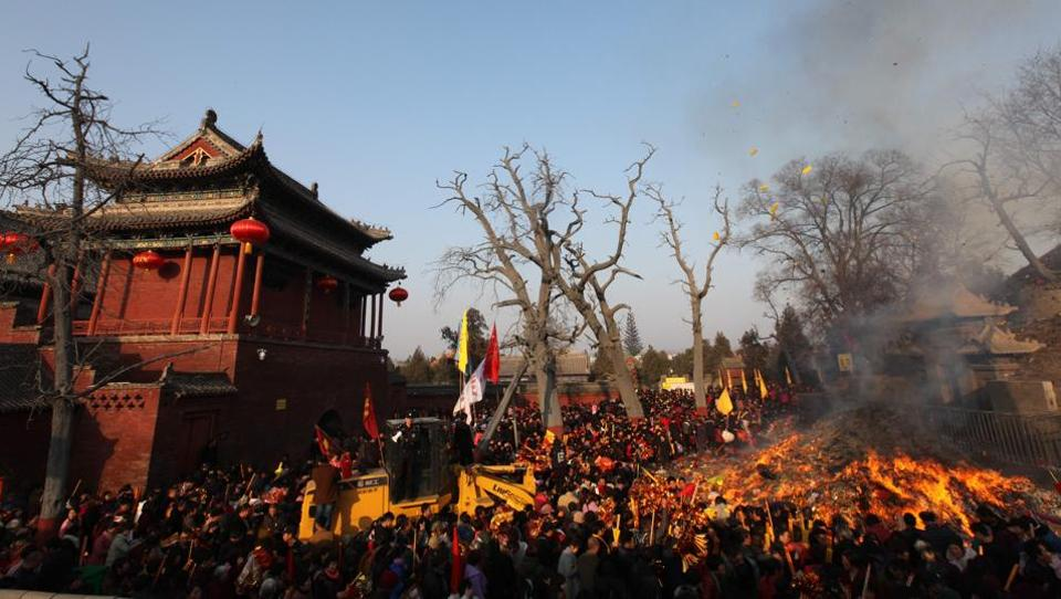 Pilgrims throwi items onto a bonfire during a temple fair at Tai Hao Tomb Temple in Huaiyang county in China's central Henan province.