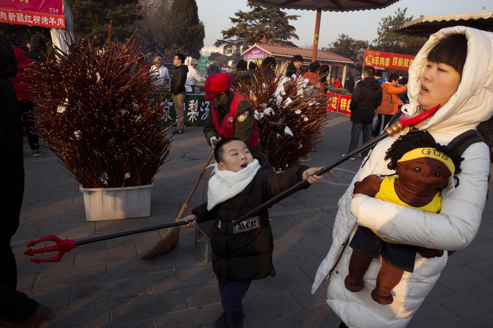 A child swings a toy weapon at a woman during a visit to a Spring Festival carnival in Beijing, China, Tuesday, Jan. 31, 2017. Residents are enjoying a week long holiday for the Chinese New Year and visiting various temple fairs and carnivals around the Chinese capital. (AP Photo/Ng Han Guan)