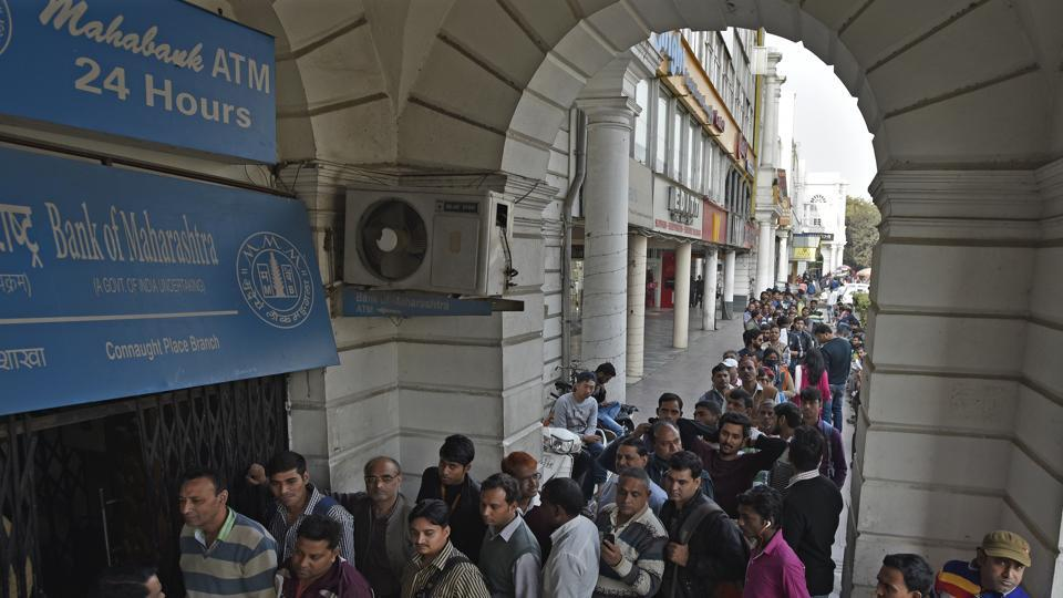 People stand in a queue at an ATMin New Delhi, December 12, 2016.  Prima facie, a shock to the cash economy lowers GDP growth as consumer spending takes a massive hit.