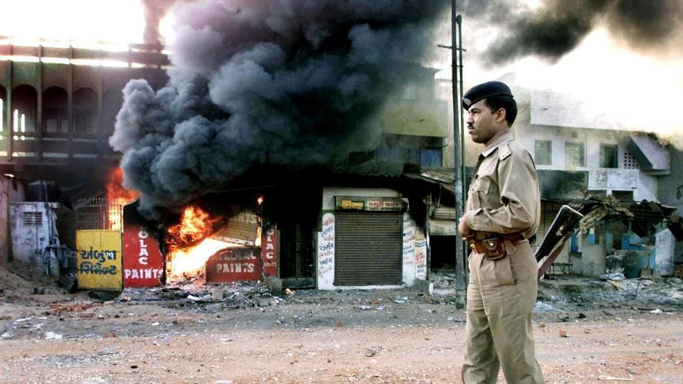 In this picture taken 01 March 2002, an Indian policeman looks on as a row of shops burns in Ahmedabad.  (AFP)