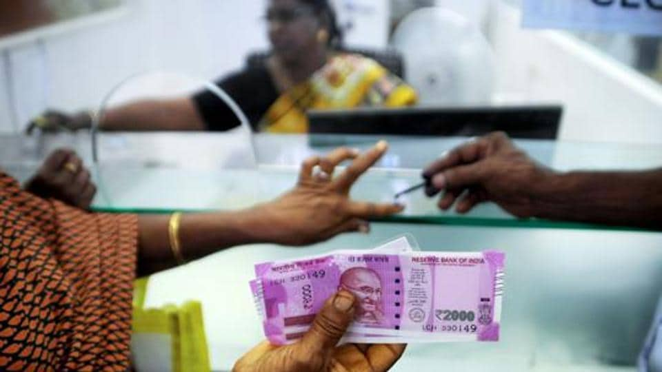 File photo taken on November 17, 2016 shows an Indian woman holding Rs 2000 notes as she has her finger marked with indelible ink after exchanging demonetised Rs 500 and Rs 1000 notes at a bank in Chennai.