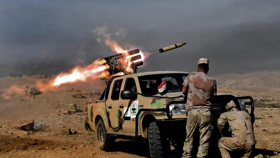 Members of the Iraqi army's 9th Division fire a multiple rocket launcher from a hill in Talul al-Atshana, on the southwestern outskirts of Mosul, on February 27, 2017, during an offensive to retake the city from Islamic State (IS) group fighters.