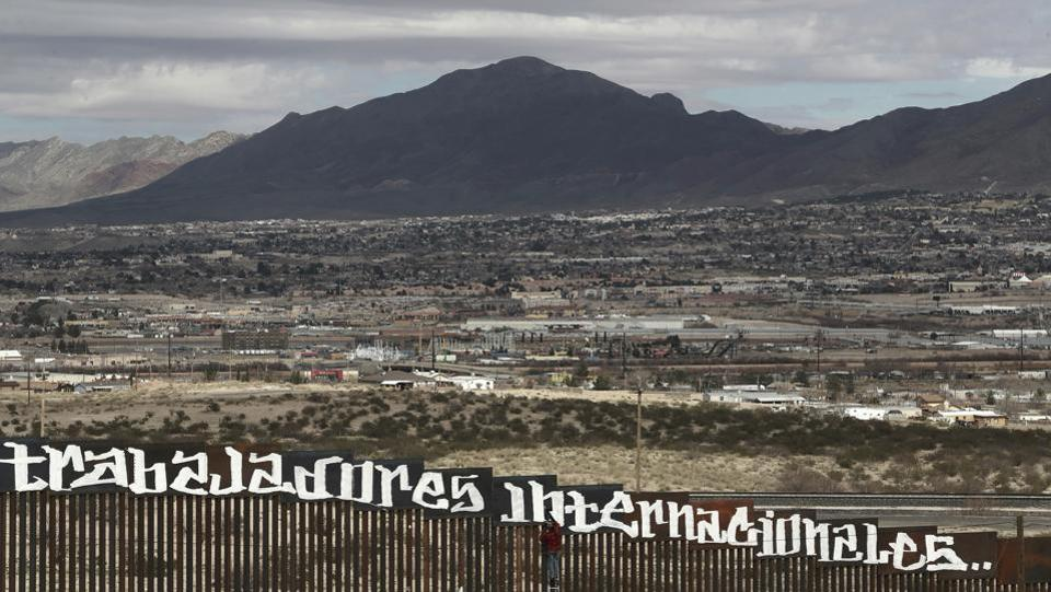 Sunland Park, New Mexico, is seen over the U.S. border fence as a protestor finishes painting the Spanish slogan