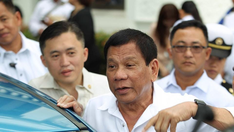 This handout photo taken on February 27, 2017 and released by the Presidential Photographers Dividion (PPD) on February 28 shows Philippine President Rodrigo Duterte (C) speaking to reporters during the launch of the first Japanese car manufacturer assembled in the country at Malacanang Palace in Manila. Duterte said on February 28 he would recall police to fight his drug war, a month after he withdrew them and denounced the force as