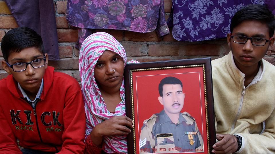 Family members of BSF head constable Rai Singh Indora holding his photograph at their residence in Kheri Sampla village in Rohtak.