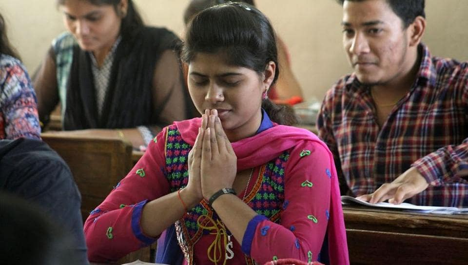 A student says a prayer before the first paper of the Higher Secondary Certificate board exams, on Tuesday. (Praful Gangurde/HT PHOTO)