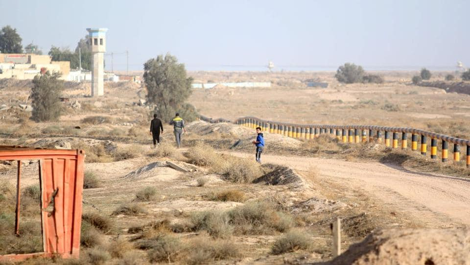Iraqis walking next to the Iraq-Kuwait border barrier near the town of Umm Qasr.  (HAIDAR MOHAMMED ALI / AFP)