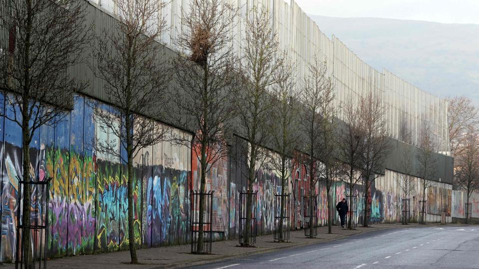 A man walking beside a peace wall in northern Belfast.  (Paul FAITH / AFP)