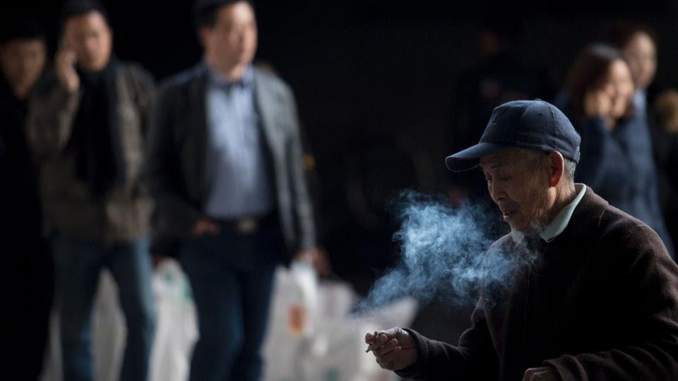 A  man smokes a cigarette at a railway station in Shanghai.