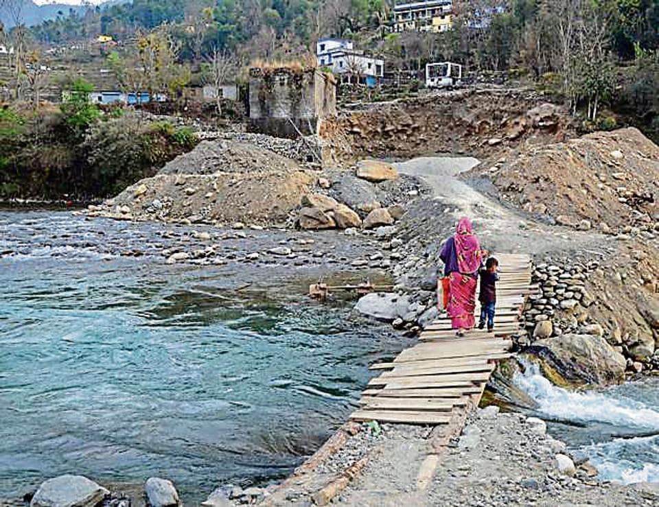 A woman and her child walk across a temporary wooden structure to cross the Pindar river.