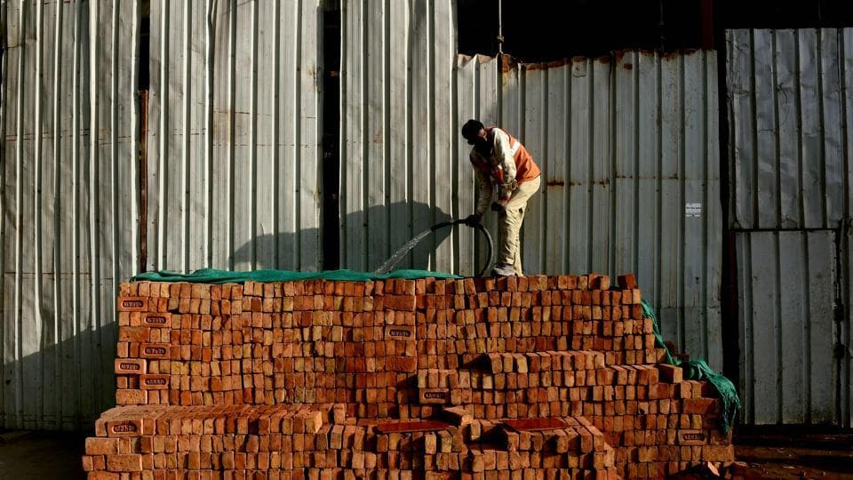 A worker waters a stack of bricks at a construction site in New Delhi. India's economic growth slowed marginally to 7% in October-December from 7.4% in the previous quarter after the controversial ban on high-value banks notes in November.