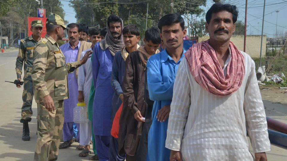 BSF personnel stand next to released Pakistani prisoners waiting to cross the India-Pakistan border at Wagah near Amritsar.