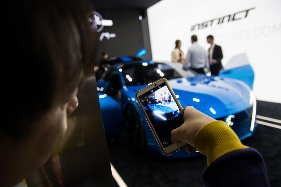 A visitor takes a picture of Peugeot car