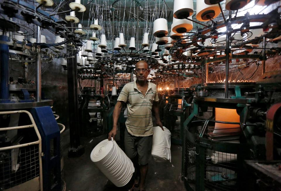 An employee carries cloth rolls inside an undergarment factory in Kolkata.