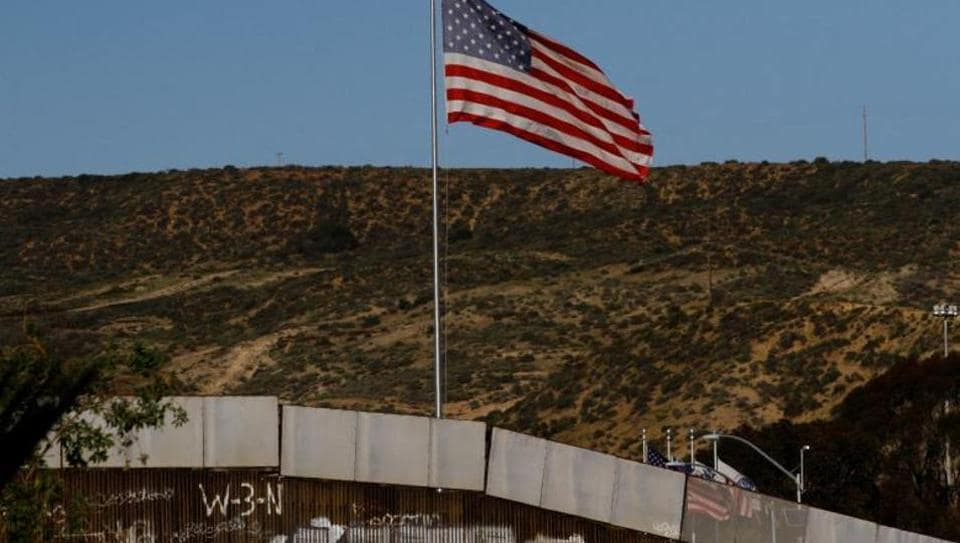 A U.S. flag is seen next to a section of the wall separating Mexico and the United States of America.