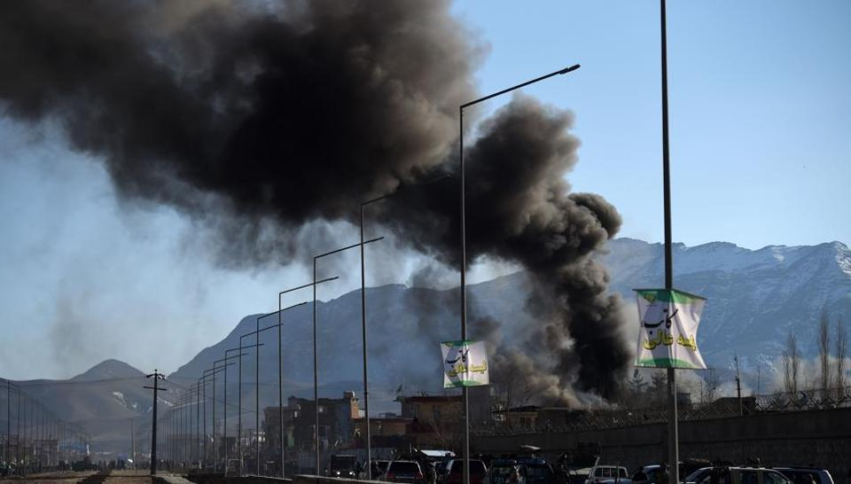 Smoke rises from an Afghan police district headquarters building after a suicide car bomb attack as a gun battle between Taliban and Afghan security forces continues in Kabul on March 1.