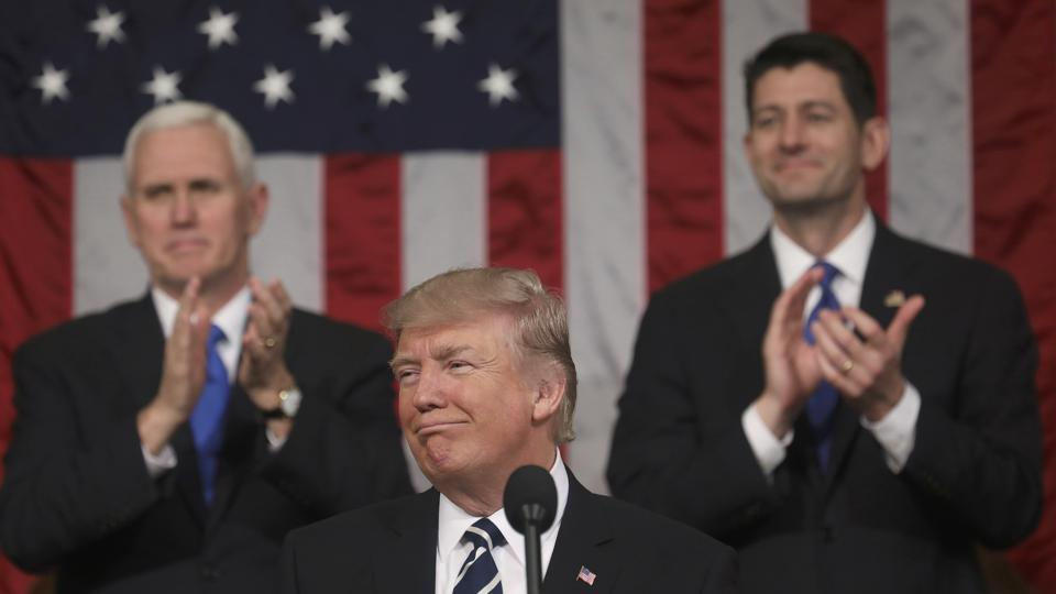 Vice President Mike Pence (L) and Speaker of the House Paul Ryan (R) applaud as US President Donald Trump delivers his first address to a joint session of Congress, Washington, February 28, 2017