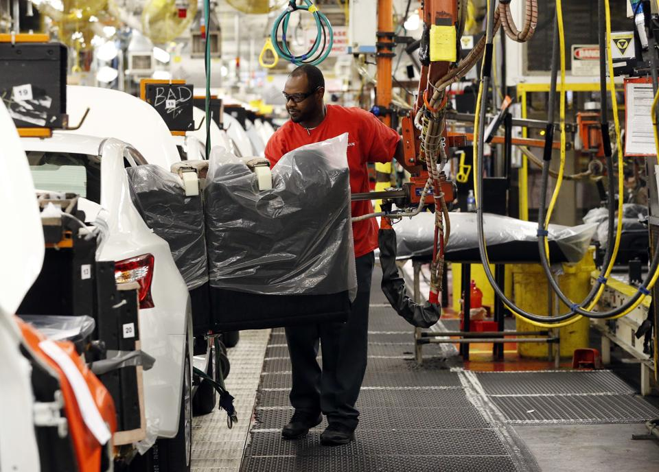 A technician uses a lift to move a back seat bench into a new Altima on the assembly line at the Nissan Canton Vehicle Assembly Plant in Canton, Mississippi.