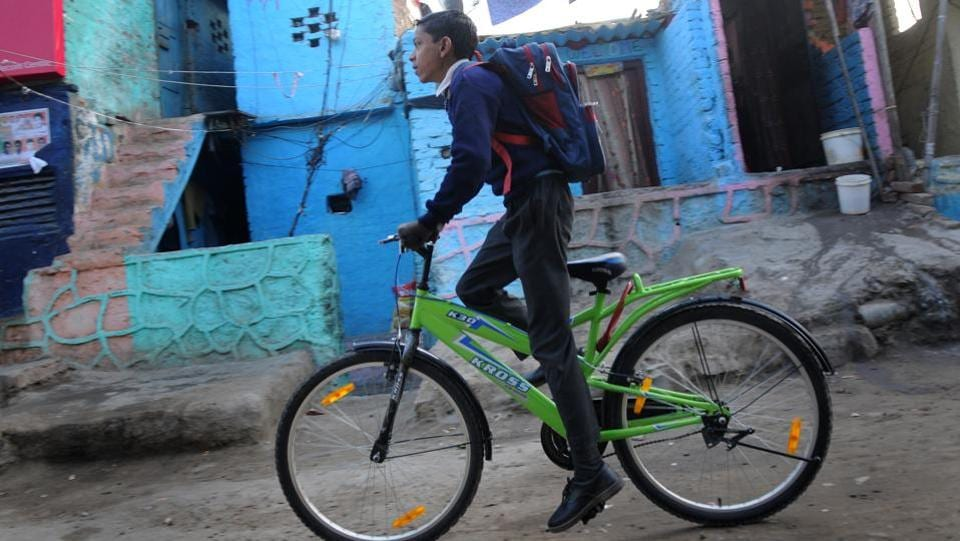 A boy leaves for school on his bicycle at a slum colony. Meanwhile, on February 6th, 350 slum dwellers who had lived for decades at the slums at Nehru Camp in east Delhi's Patparganj were allotted flats in Sector 16B in Dwarka, which is many miles away.  (Burhaan Kinu/HT PHOTO)