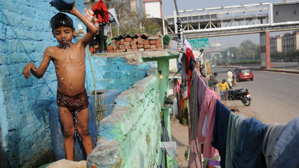 A child bathes upon return from school at Sector 16 slum colony, in Noida. Living in a slum life often means going without basic sanitation facilities. It remains to be seen whether the initiative will help slum dwellers find a better quality of life.  (Burhaan Kinu/HT PHOTO)