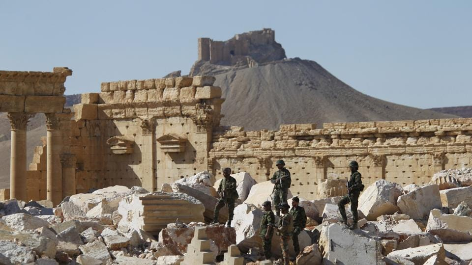 Syrian army soldiers stand on the ruins of the Temple of Bel in the historic city of Palmyra, in Homs Governorate, Syria April 1, 2016.
