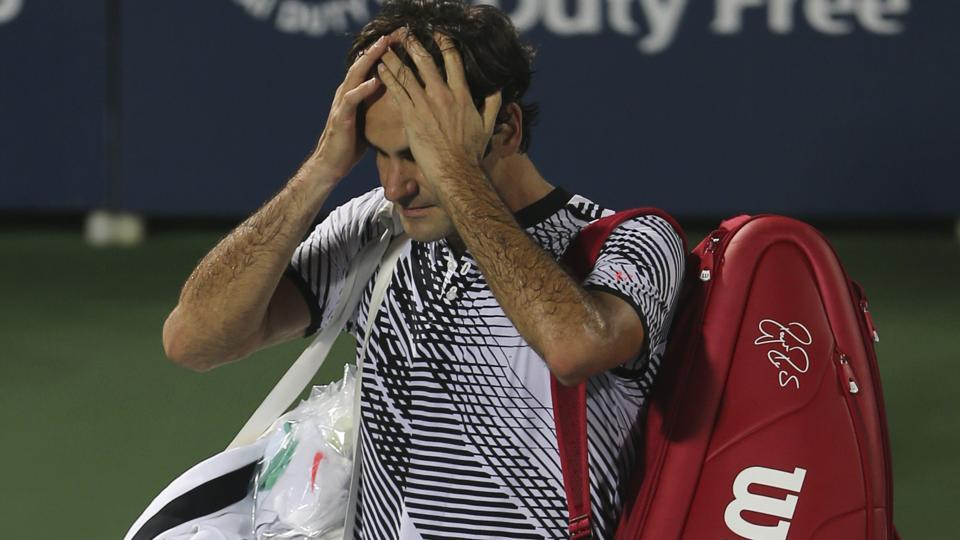 Roger Federer  gestures as he leaves the court after losing to Evgeny Donskoy at Dubai Tennis Championships.