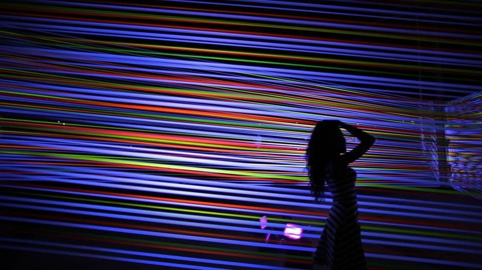 A woman poses in front of a light art piece titled 'Horizontal Interference' by artists Katarzy Malejka and Joachim Stugocki of Poland. (Wong Maye-E / AP)