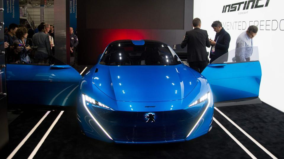 Visitors look at the Peugeot car 'Instinct', connected by Samsung technology (AFP)