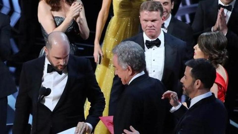 Martha Ruiz (R, in red) and Brian Cullinan (upper R) of PricewaterhouseCoopers confer on stage after the Best Picture was mistakenly awarded to La La Land instead of Moonlight.