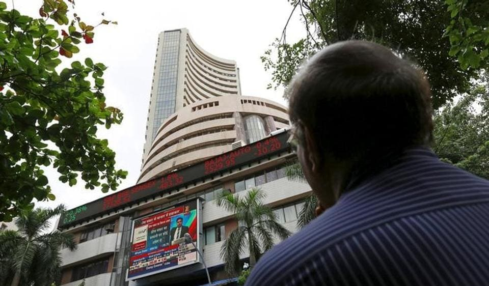 A man looks at a screen across a road displaying the Sensex on the facade of the Bombay Stock Exchange (BSE) building in Mumbai, India.