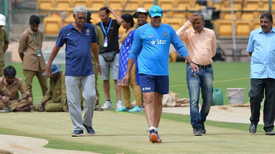 India cricket team coach, Anil Kumble (centre) takes a close look at the Chinnaswamy Stadium pitch during training on Thursday. The second Test against Australia cricket team begins inBangalore on Saturday.With the Pune pitch (first Test) termed as 'poor' by the ICCmatch referee, there will be a lot of attention on how the Bangalore Test pitch plays, the hope being that the match lasts five days.