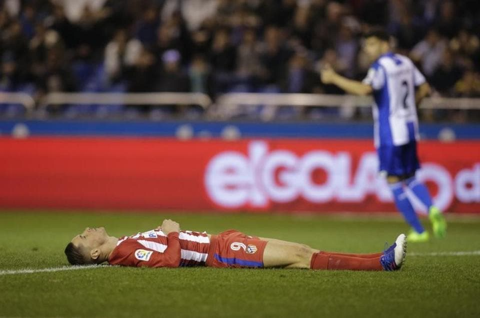 Fernando Torres of Atletico Madrid  lies on the field after colliding during a Spanish league football match vs Deportivo de la Coruna at the Municipal de Riazor stadium in La Coruna on Thursday.