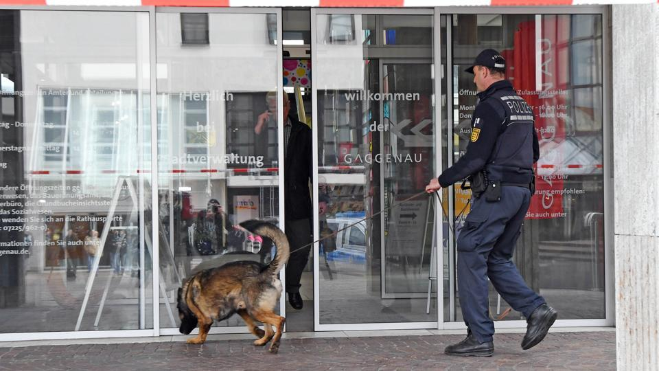 A policeman with a sniffer dog in Gaggenau, southwestern Germany, which received a bomb threat after blocking a rally by Turkey's justice minister.