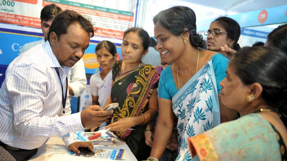 A bank employee explains mobile banking features to customers at a bank in Hyderabad.