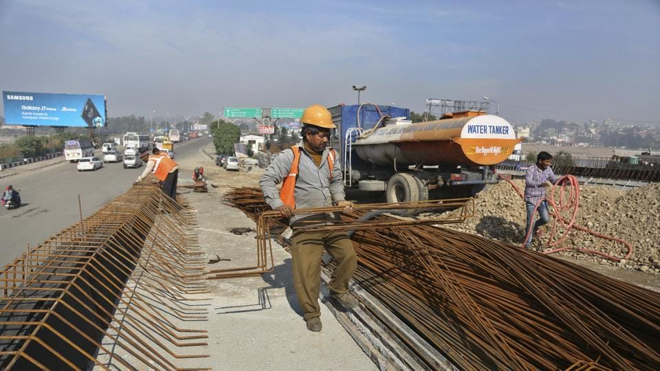 Laborers work at a flyover construction site in Jammu.