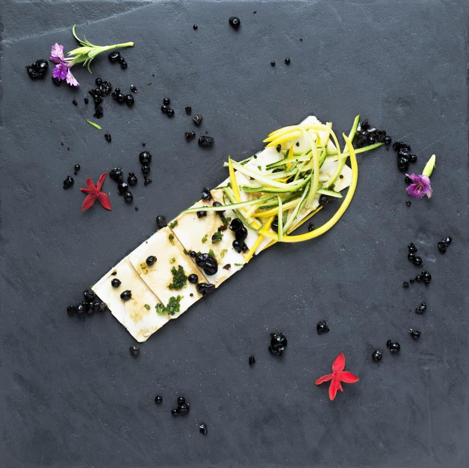 Tofu carpaccio with a soya sauce drizzle and edible flowers, served on slate or stone.