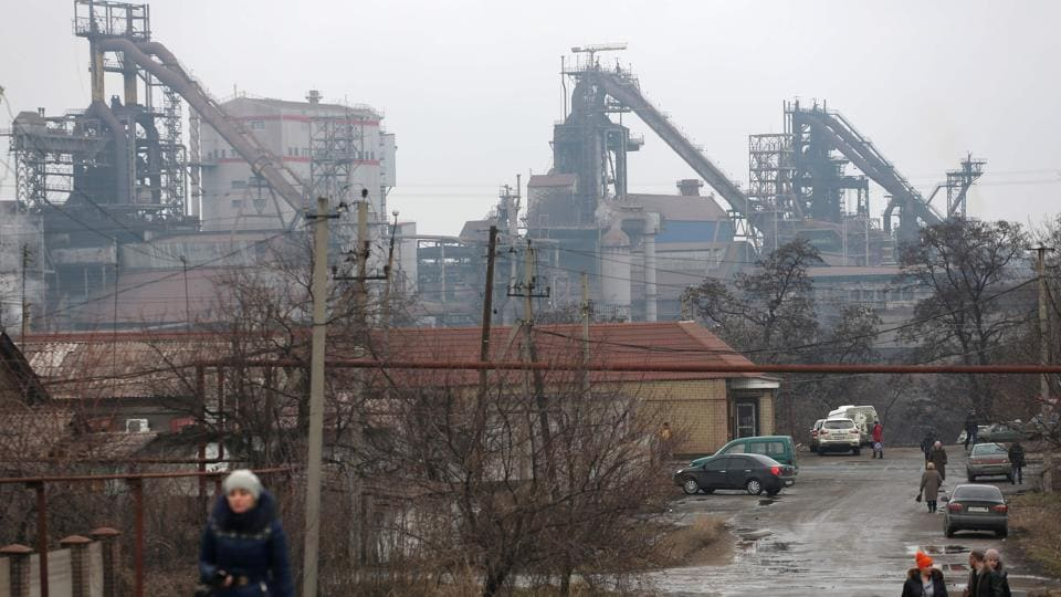 People walk in front of Metallurgical Works plant in Yenakiyeve, Donetsk. Russian-backed rebels on March 1, 2017 halted the operations of the first Ukrainian company after an ultimatum expired to end a trade blockade between the two foes.
