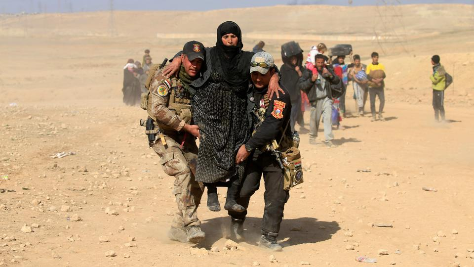 Iraqi security forces help a displaced Iraqi woman flee her home as Iraqi forces battle with Islamic State militants in western Mosul. (Alaa Al-Marjani / REUTERS)