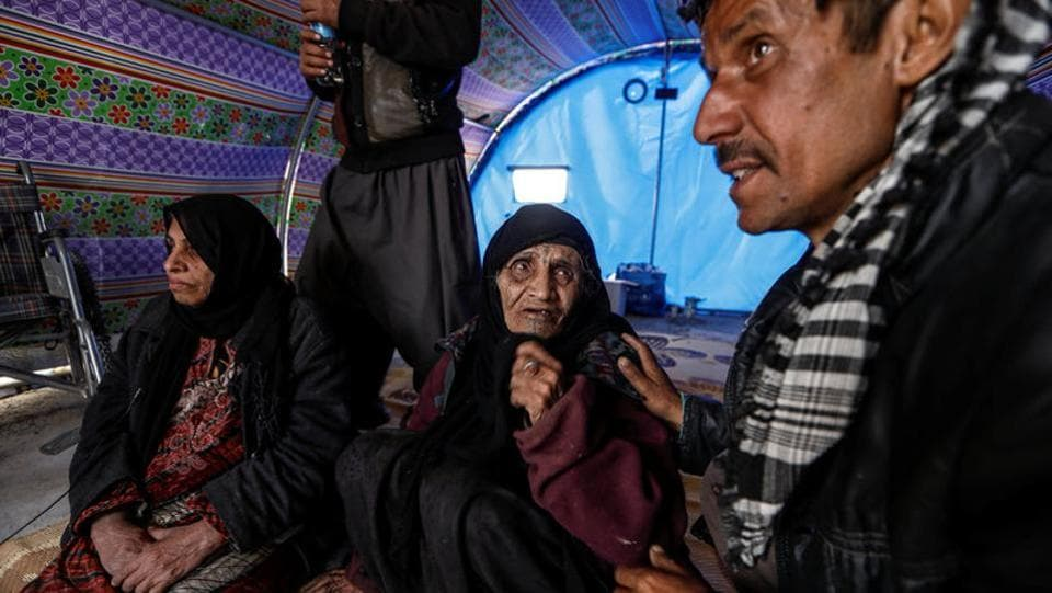 "Khatla Ali Abdullah, 90, who recently fled her home in Al Mamoun district talks to her relative as she sits with her daughter (L) in her tent in Hammam al Alil camp. I haven't lost any chickens, not even a one little chick,"" she said. We were trapped in the basement and we could hear the bullets hitting the metal roof of the chicken pen. (Zohra Bensemra/REUTERS)"