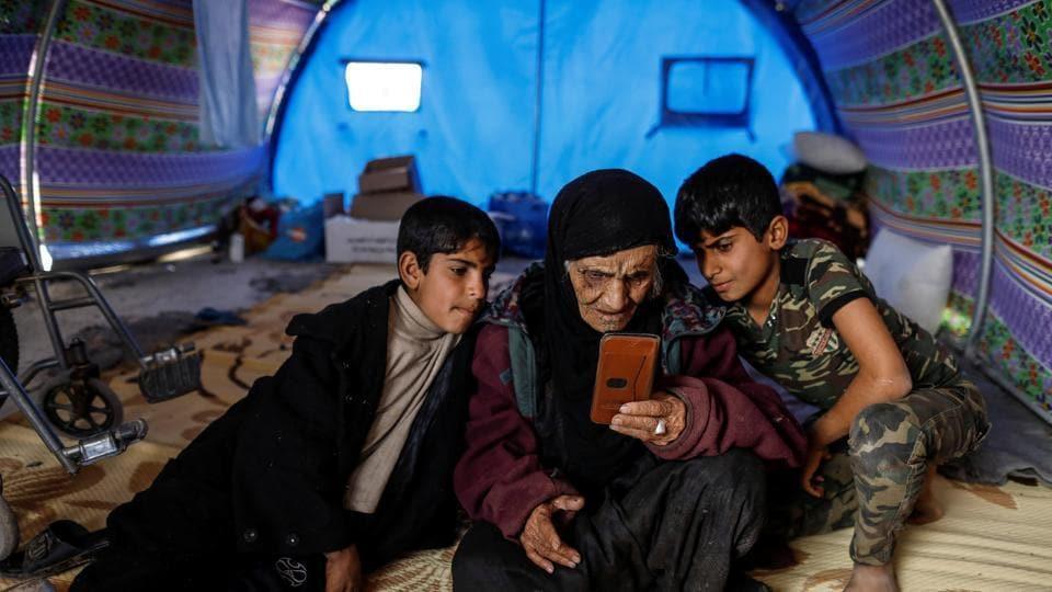 Khatla Ali Abdullah , 90, who recently fled her house in Al Mamoun district looks at photographs on a mobile phone as she sits with her grandsons in her tent in Hammam al Alil camp while Iraqi forces battle with Islamic State militants, in western Mosul, Iraq March 1, 2017.