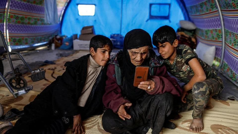 Khatla Ali Abdullah , 90, who recently fled her house in Al Mamoun district looks at photographs on a mobile phone as she sits with her grandsons in her tent in Hammam al Alil camp. Even under the Saddam era, we were afraid because of the atrocities and the people killed, she said. But nothing is compared to this phase. (Zohra Bensemra/REUTERS)