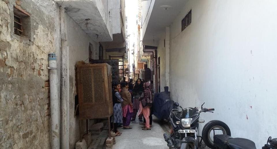 People gather in front of the house of the victim in  southwest Delhi's Bindapur.